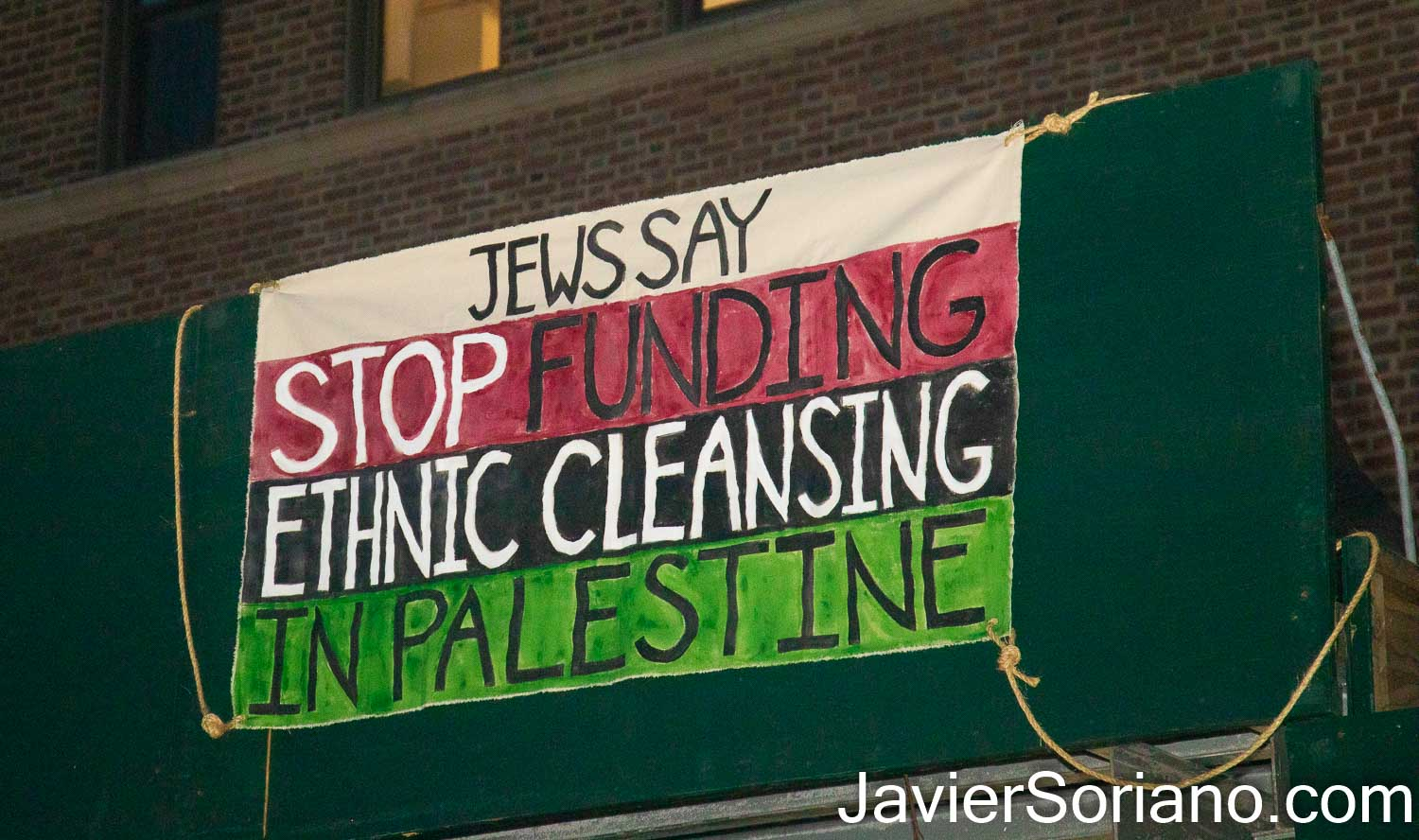 """Friday, May 21, 2021. New York City – Jews, Palestinians and other New Yorkers gathered at Grand Army Plaza in the borough of Brooklyn to stand in solidarity with Palestine. After the rally, demonstrators marched to the building of the United States Senator Charles Ellis Schumer. The luxury building is in front of Prospect Park. Protesters hung a banner in front of the senator's building that reads: """"Jews say stop funding ethnic cleansing in Palestine."""" Photo by Javier Soriano/www.JavierSoriano.com"""