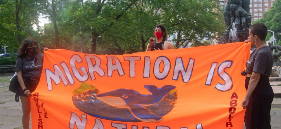 """Saturday, July 10, 2021. New York City – On Saturday, July 10, 2021, the organization Autonomous Brown Berets Of NYC held marches in the boroughs of Queens, Bronx and Brooklyn, in New York City. The demonstrations were to denounce the 600,000 deportations and expulsions of undocumented immigrants by Joe Biden and Kamala Harris. THIS PHOTO: People at Grand Army Plaza, Brooklyn. The Banner reads, """"Migration is natural. Abolish ICE. Land back. Resist Line 3."""" Photo by Javier Soriano/JavierSoriano.com"""