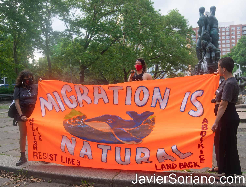 """Sábado 10 de julio de 2021. Ciudad de Nueva York – El sábado 10 de julio de 2021, la organización Autonomous Brown Berets Of NYC realizó tres marchas en tres diferentes condados en la ciudad de Nueva York. Las manifestaciones fueron para denunciar las 600,000 deportaciones y expulsiones de inmigrantes indocumentados por parte del gobierno de Joe Biden y Kamala Harris. ESTA FOTO: Gente en Grand Army Plaza, Brooklyn. El Banner dice: """"La migración es natural. Abolir ICE. Regresen la tierra. Resistir la línea 3."""" Foto por Javier Soriano/JavierSoriano.com"""